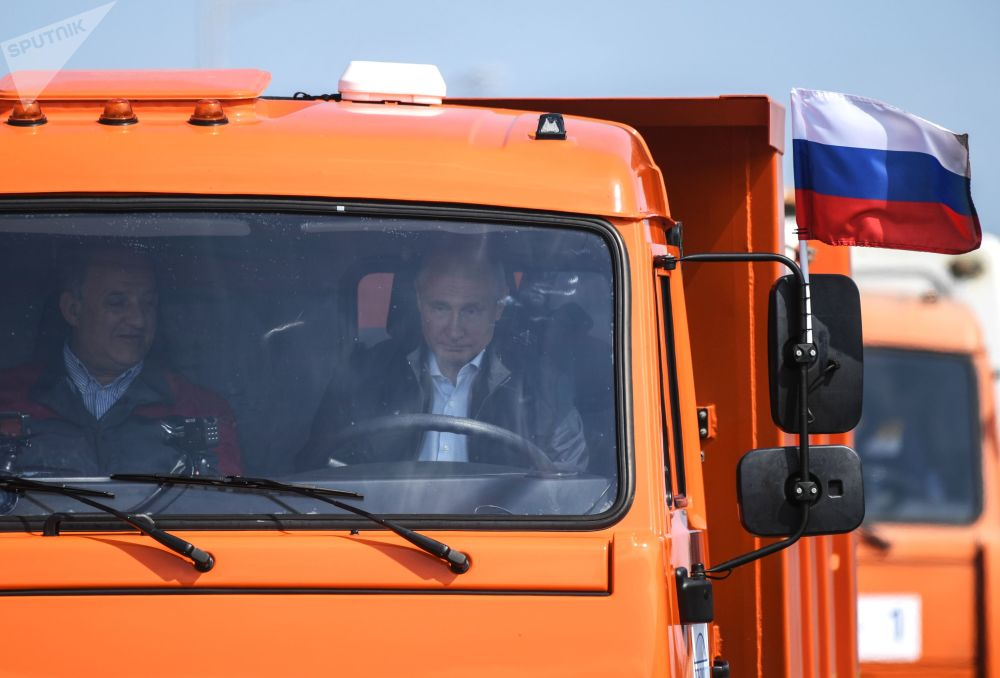 Il presidente russo Vladimir Putin guida una Kamaz attraverso il ponte di Crimea.