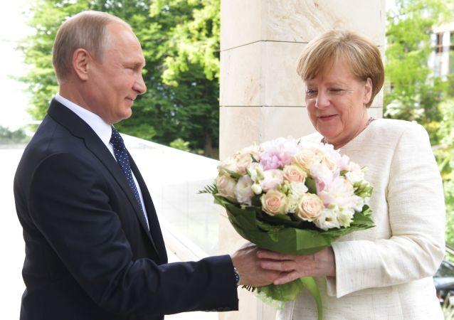 Putin regala un mazzo di fiori ad Angela Merkel