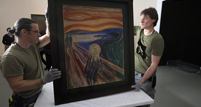 In this photo taken on Wednesday, March 18, 2015, employees present the painting The Scream by Edvard Munch, prior to it being exhibited, at the Louis Vuitton Foundation in Paris, France.
