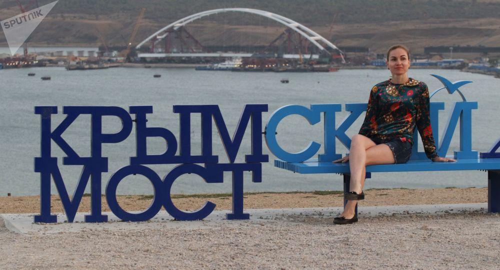 Девушка на скамейке с надписью Крымский мост на горе Митридат в Керчи