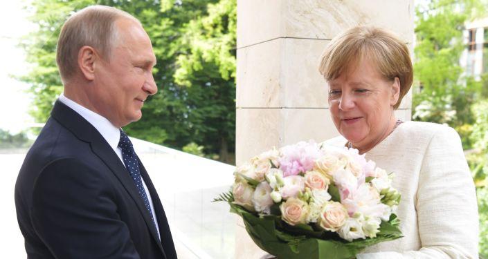 Il presidente Putin regala dei fiori al cancelliere tedesco Angela Merkel