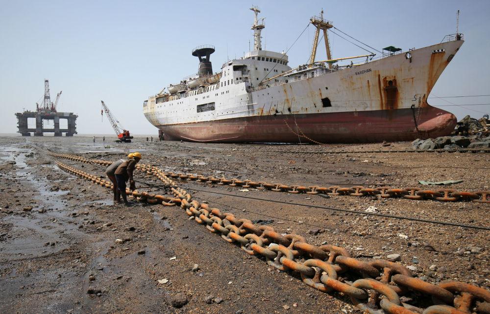 I lavoratori stringono la corda legata alla torre di estrazione del petrolio fuori uso in India.