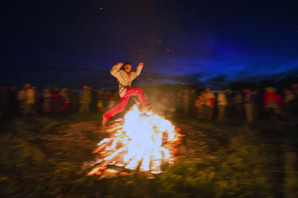 Salto sul fuoco alla festa del Solstizio d'Estate nel villaggio di Okunevo, vicino Omsk