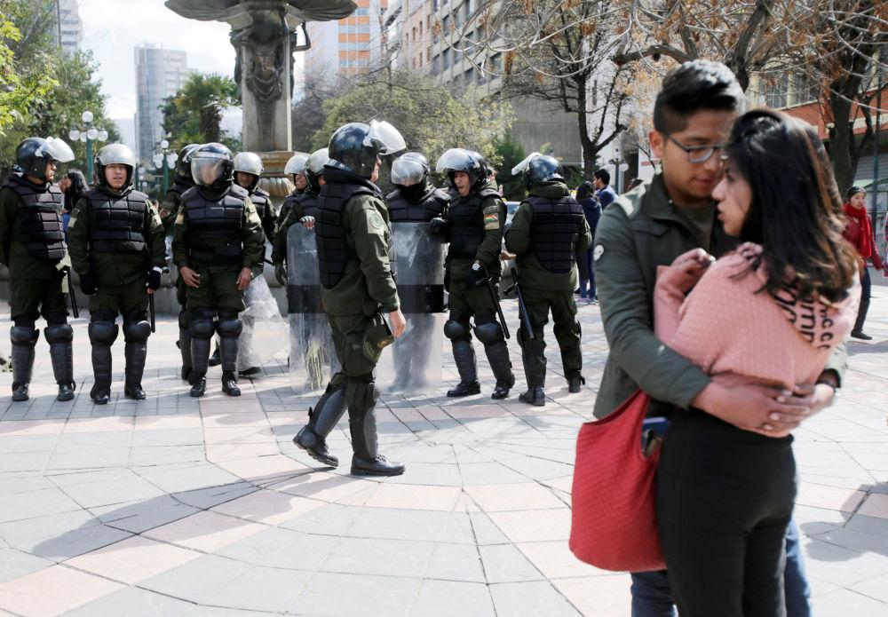 Una coppia sta vicino ai poliziotti che si stanno preparando alle proteste dell'Università UPEA a La Paz, Bolivia
