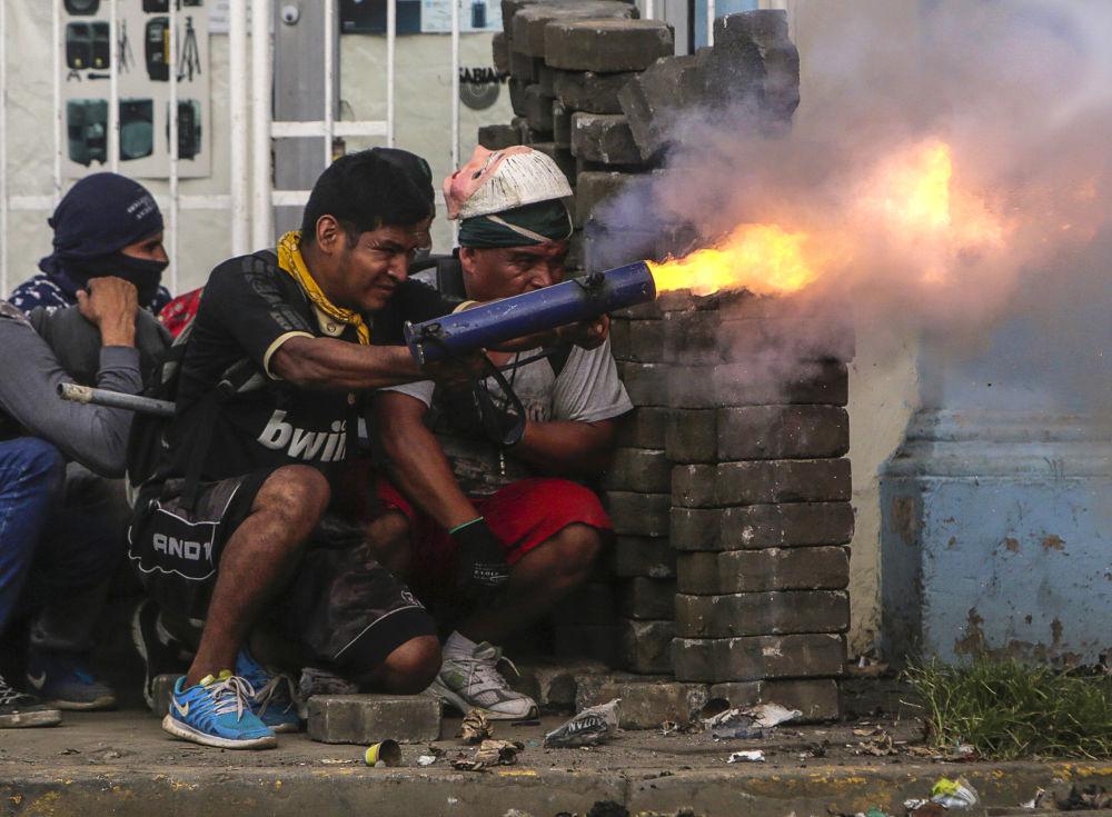 Un manifestante antigovernativo apre fuoco durante gli scontri con la polizia a Masaya, Nicaragua.