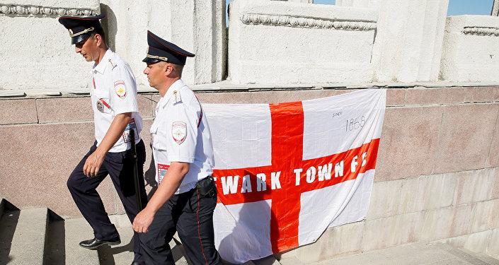 Poliziotti russi camminano davanti ad una bandiera inglese appesa dai tifosi a Volgograd