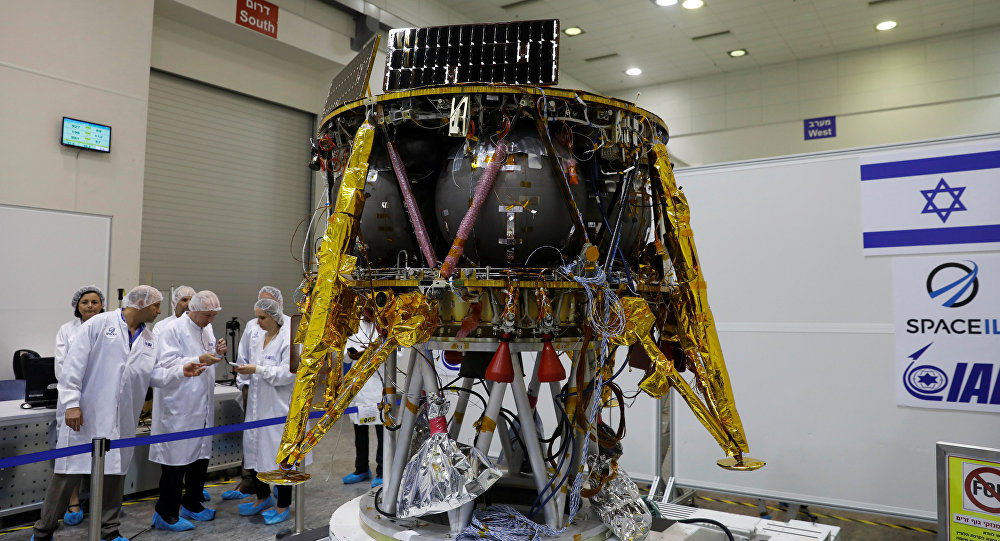 Israeli scientists stand next to an unmanned spacecraft which an Israeli team plans to launch into space at the end of the year and to land it on the Moon next year, in Yahud, Israel, July 10, 2018