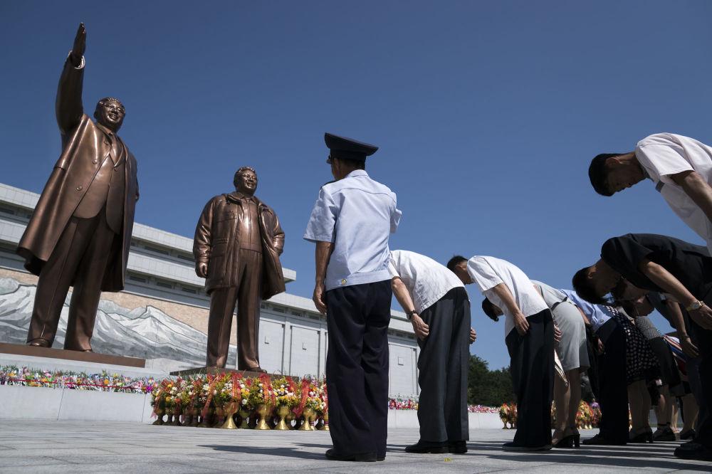 La gente rende omaggio a Kim Il Sung, a sinistra, e Kim Jong Il, Pyongyang, Corea del Nord.