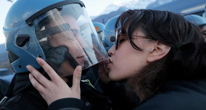 Una manifestante bacia un poliziotto durante una protesta a Susa contro il TAV tra Lione e Torino