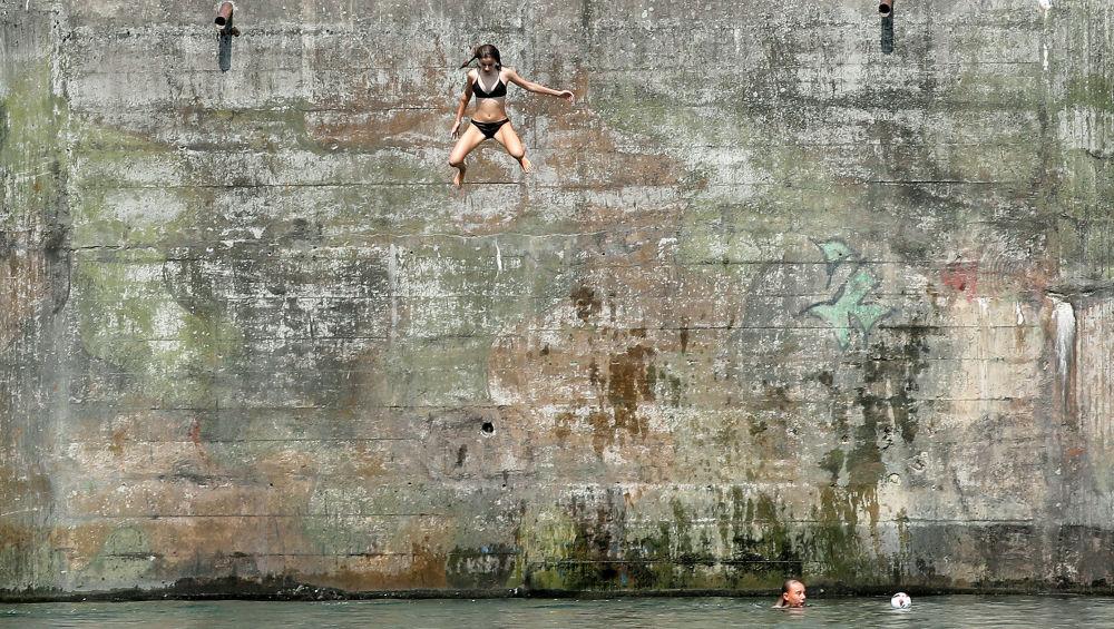 Una ragazza salta nel fiume Reno, Svizzera.