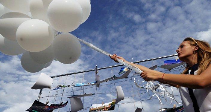 Una ragazza di Donetsk lancia in aria un palloncino bianco durante una manifestazione per la pace
