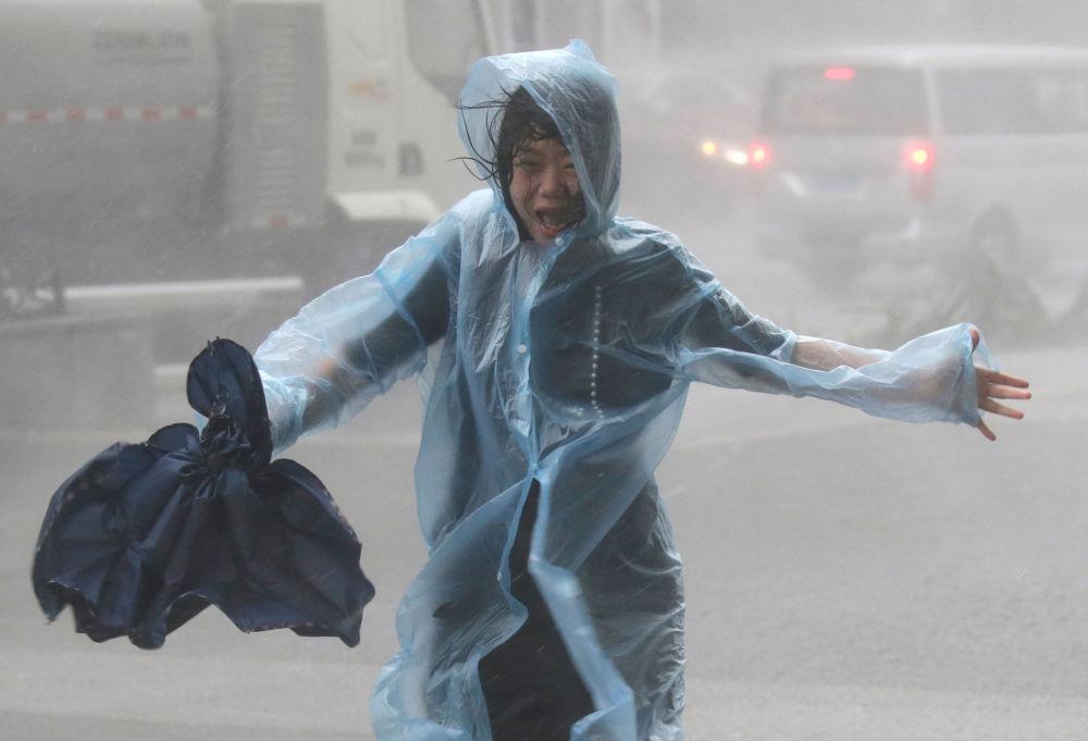 Una donna nella pioggia causata dal typhoon Mankhut in Cina