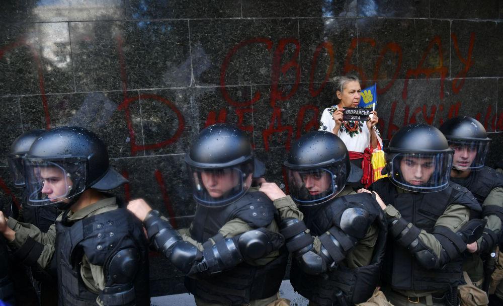 Una donna sta dietro i poliziotti alla sede della procura generale dell'Ucraina