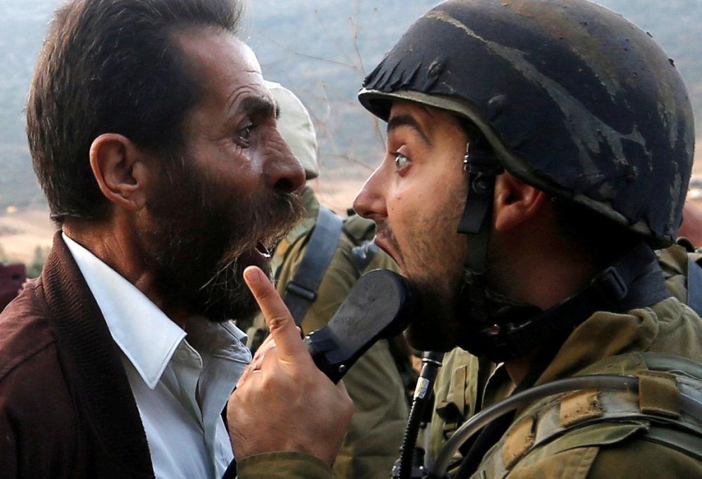 Un palestinese litiga con un soldato israeliano durante gli scontri nei pressi di Nablus.
