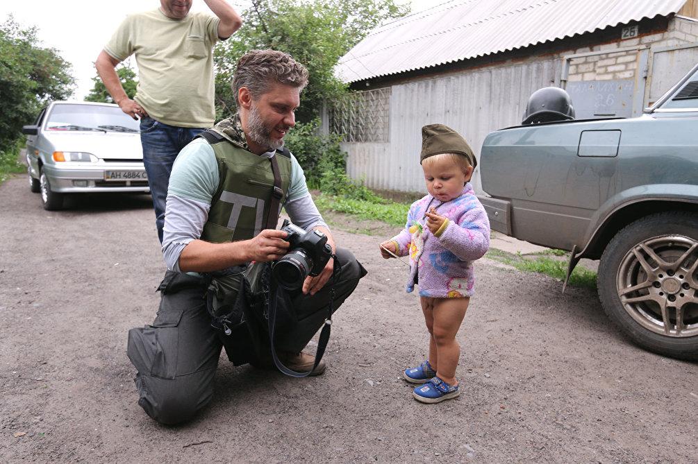 Andrey Stenin con un bambino nel villaggio di Semenovka, nel Donbass.