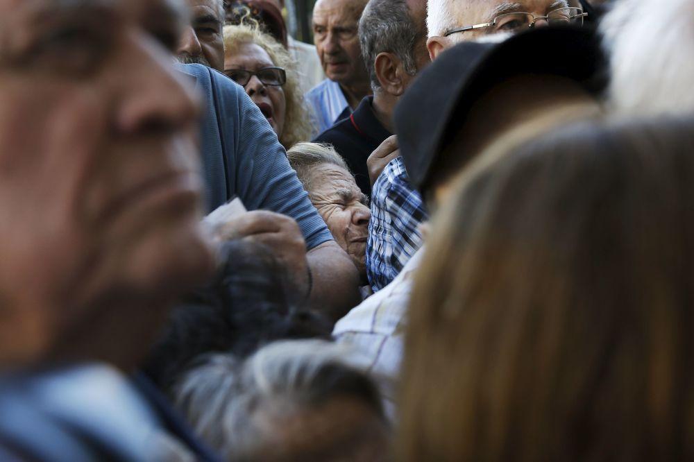 Pensionati fanno la coda a un filiale della Banca Nazionale Greca.