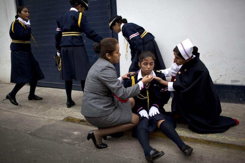 Insegnanti cercano di ravvivare una ragazza svenuta durante la parata in onore del Giorno di San Pedro a Lima.