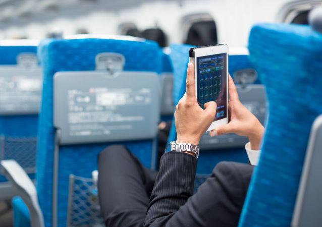 Passeggero con smartphone a bordo di aereo