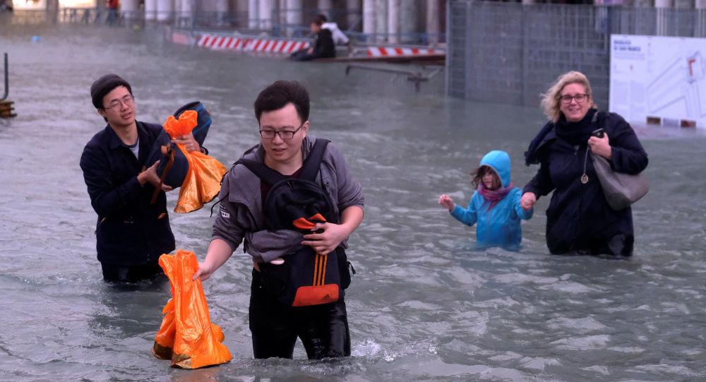Turisti immersi nell'acqua alta a Venezia