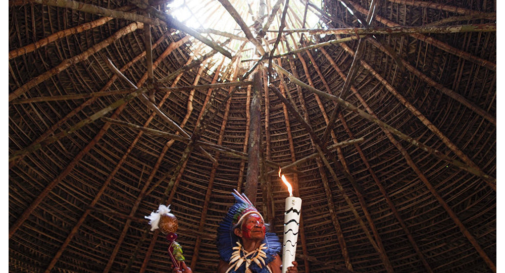 Dessana indigenous shaman Raimundo Dessana holds the Olympic Torch during a ritual at the Tupe Reservation in the outskirts of Manaus, Amazonas, Brazil, on June 20, 2016