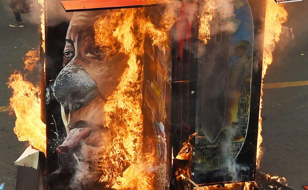 Il ritratto del presidente filippino Rodrigo Duterte in fiamme durante una manifestazione a Manila.