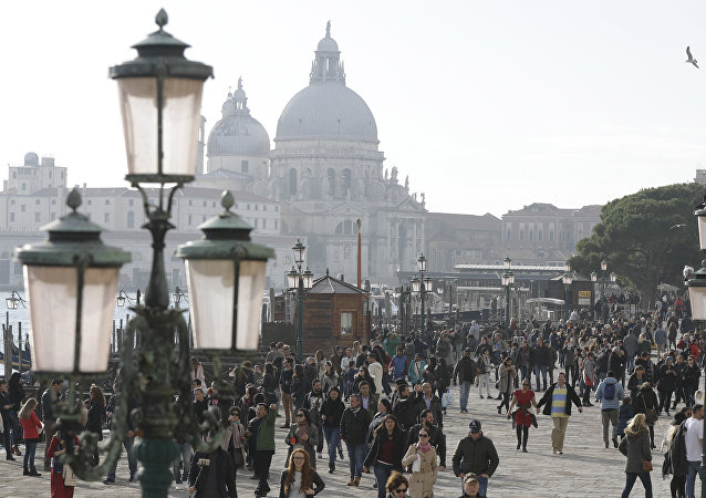 Tourists stroll in downtown Venice, Italy, Saturday, Nov. 12, 2016. Since 1951, Venice's population has steadily shrunk from 175,000 to some 55,000. Several factors are blamed, including high prices driven by a boom in tourism, the logistics of supplying a carless city, and the erosion of canal-side apartment buildings by lapping waters