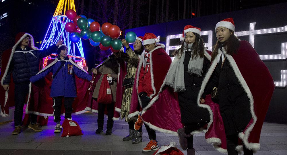 Giovani cinesi vestiti come gli aiutanti di Babbo Natale a Pechino, Cina.