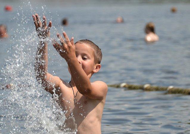Bambino alla spiaggia del laghetto di Akademiceska presso la Moscova