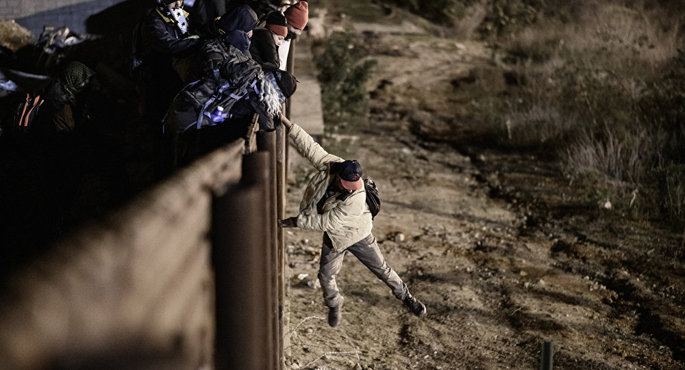A migrant jumps the border fence to get into the U.S. side to San Diego, Calif., from Tijuana, Mexico, Tuesday, Jan. 1, 2019