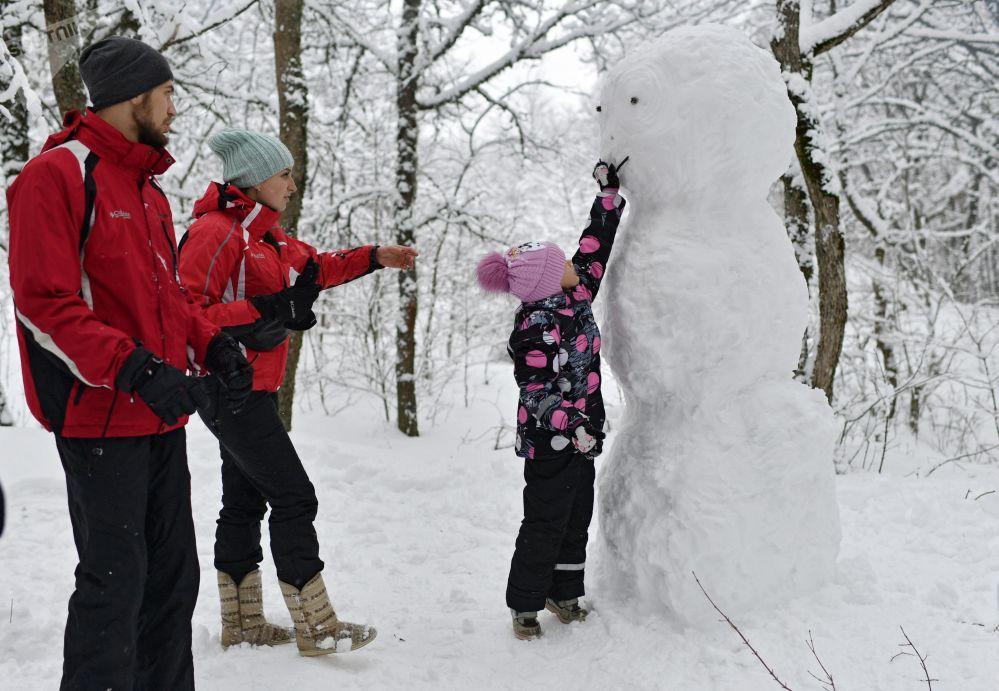 Una famiglia ed un pupazzo di neve al passo di Angarskij.