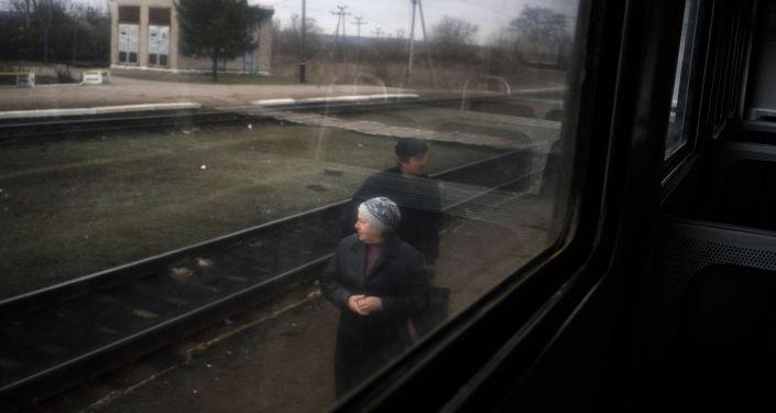Due anziani aspettano il treno locale Yasinovataya-Lugansk