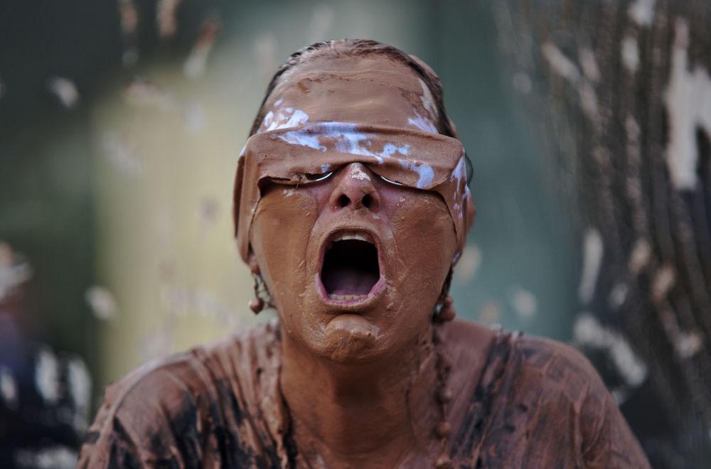 Una donna coperta dal fango durante le proteste davanti alla sede della compania mineraria brasiliana Vale a Rio de Janeiro.