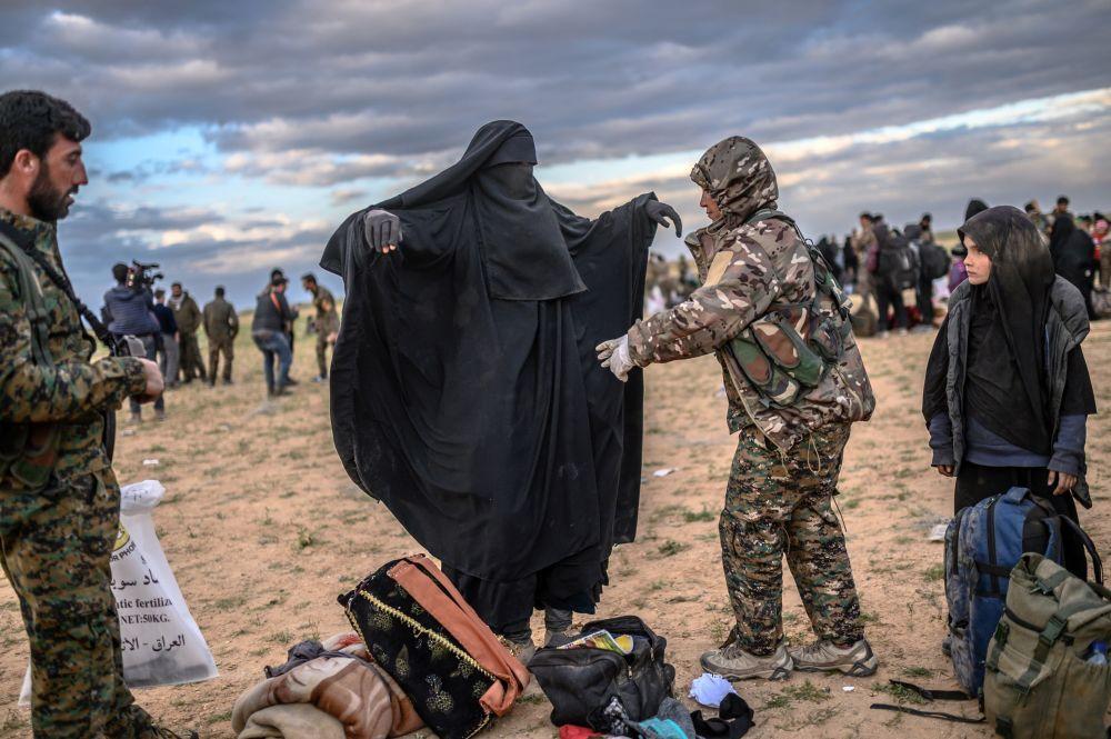 Membro delle Forze Siriane Democratiche fà prequisizione delle persone che hanno lasciato l'ultima basa del Daesh a Baghouz.