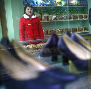 Una commessa in un negozio di scarpe di Pyongyang