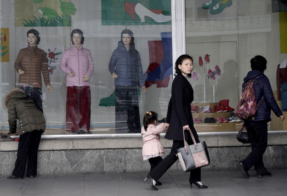 Una donna tiene per mano sua figlia a passeggio davanti ad una vetrina di un negozio d'abbigliamento a Pyongyang
