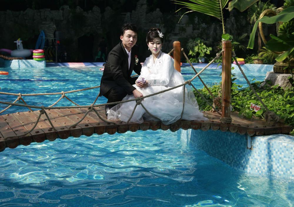 Una coppia di sposini posa per una foto del servizio di nozze in una piscina di Pyongyang