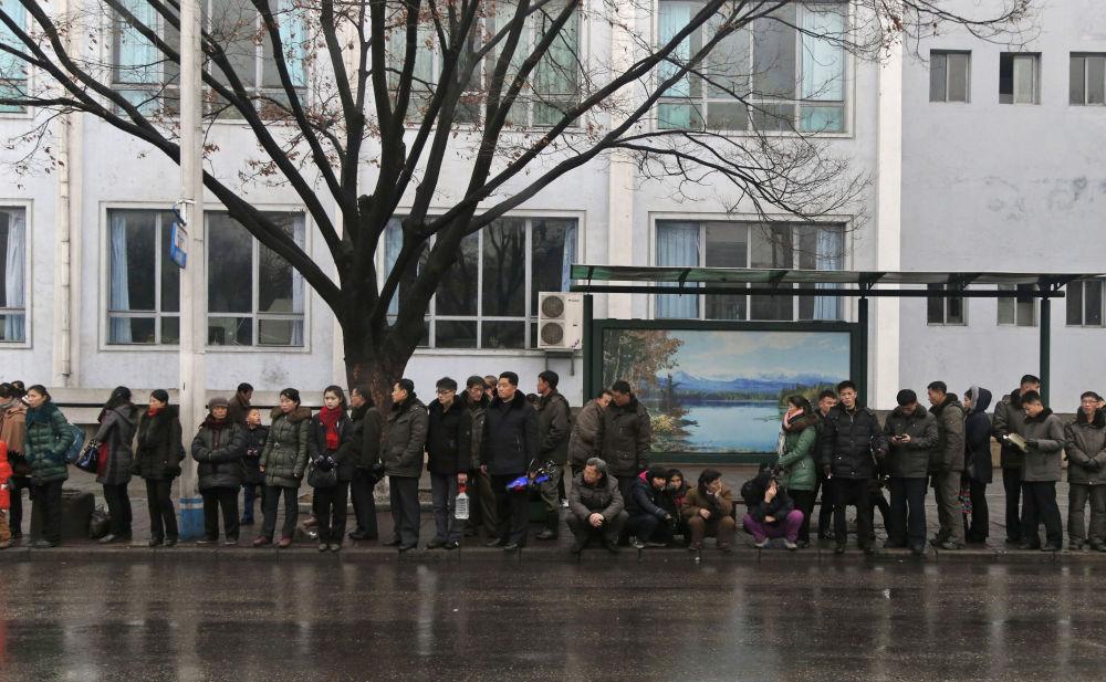 Persone in coda alla fermata del pulmann di Pyongyang