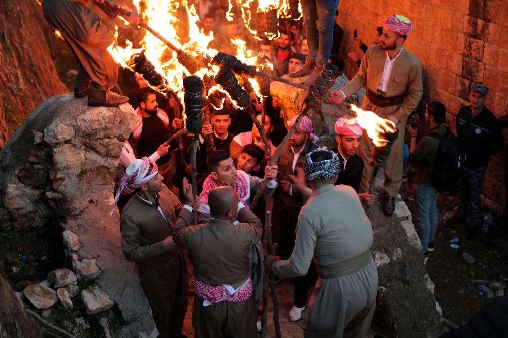 Curdi iracheni accendono delle torce: il fuoco, simbolo di calore, luce e rinascita è uno dei principali attributi della festa del Nowruz