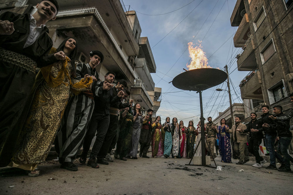 Uomini e donne curde nei propri costumi tradizionali celebrano il Nowruz con una danza intorno al fuoco nella città di Qamishly, in Siria