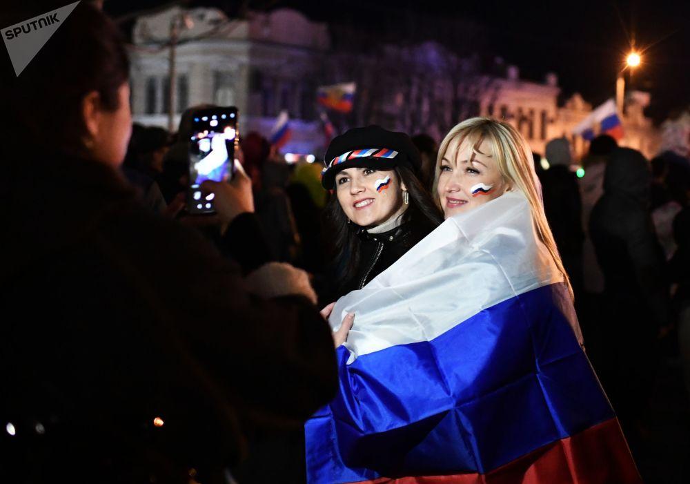 Gli spettarori fanno le foto durante il concerto per il quinto anniversario dell'adesione della Crimea alla Russia.