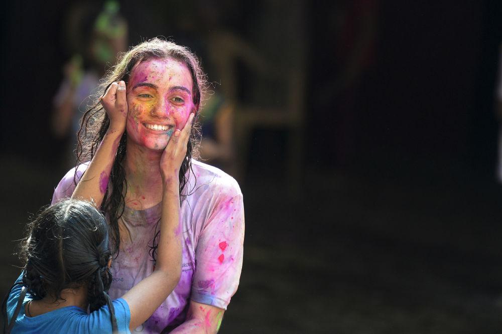Una studentessa indiana non vedente della Devnar School for the Blind lancia polvere colorata a un insegnante mentre celebra il festival di Holi a Hyderabad il 21 marzo 2019. Holi è il popolare festival di colori indù della primavera che si festeggia in India alla fine di la stagione invernale durante ll'ultima luna piena del mese lunare.