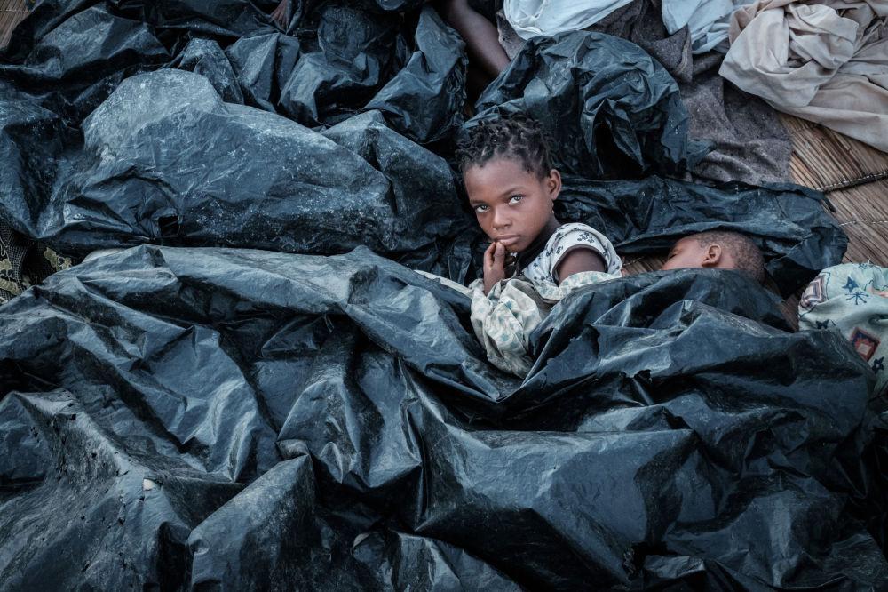 Enia Joaquin Luis, di 11 anni, con sua sorella Luisa, di 6 anni , si nascondono sotto le lastre di plastica per proteggersi dopo il ciclone che ha colpito il Mozambico.