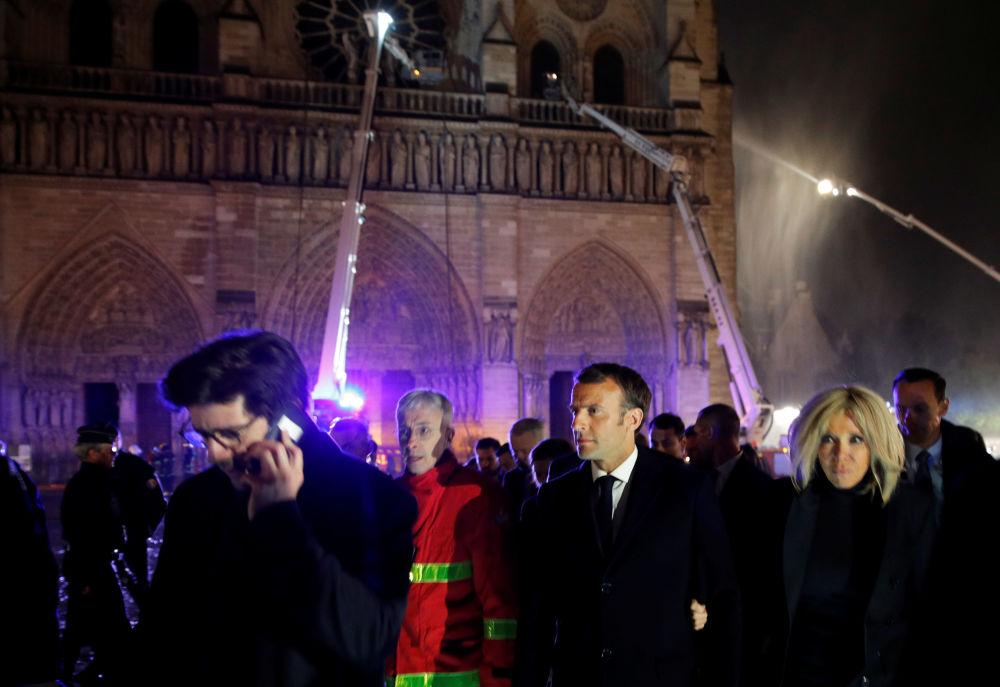15 aprile 2019 - Il presidente francese Emmanuel Macron insieme alla moglie Brigitte davanti alla cattedrale di Notre Dame in fiamme