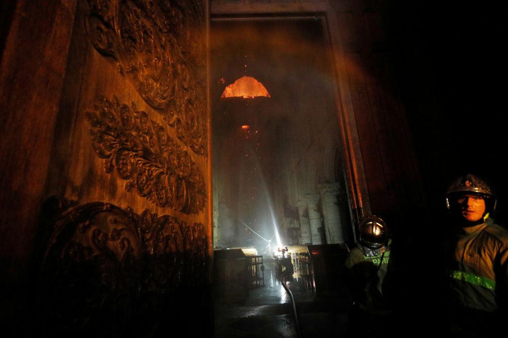Pompieri al lavoro per spegnere le fiamme dall'esterno della cattedrale di Notre Dame