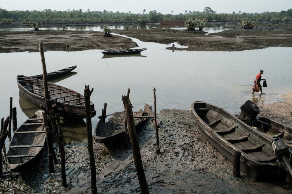 Un pescatore nell'acqua sporca nel villaggio di Ogoniland, sul delta del fiume Niger, in Nigeria