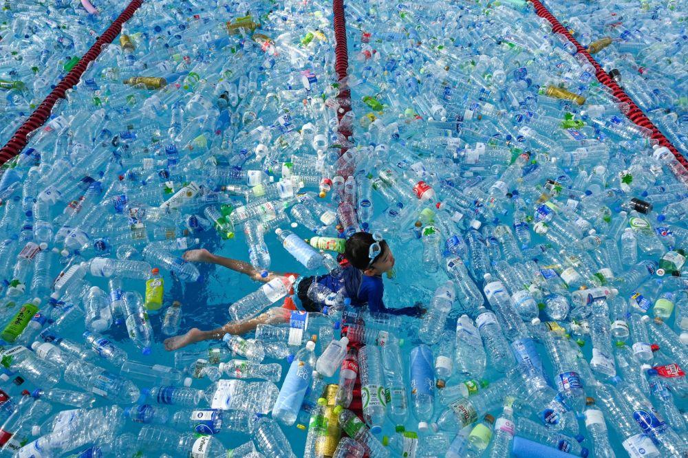Bambino nuota nella piscina riempita con delle bottiglie di plastica durante la campania dedicata alla Giornata Mondiale degli Oceani a Bangkok, in Thailandia.