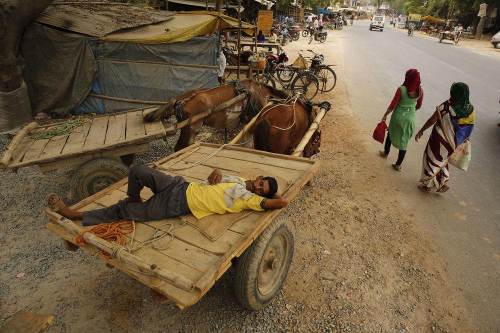 Uomo dorme in un carretto durante un'ondata di caldo anomalo in India.