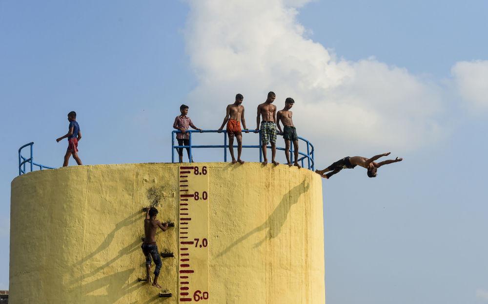 Nuotata nel fiume Buriganga in un giorno caldo a Dhaka, Bangladesh.