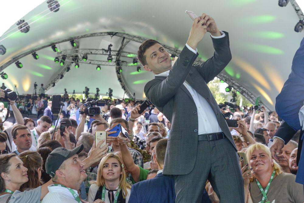 Il presidente ucraino Vladimir Zelensky si fa un selfie al primo congresso del suo partito nel giardino botanico comunale a Kiev, Ucraina.