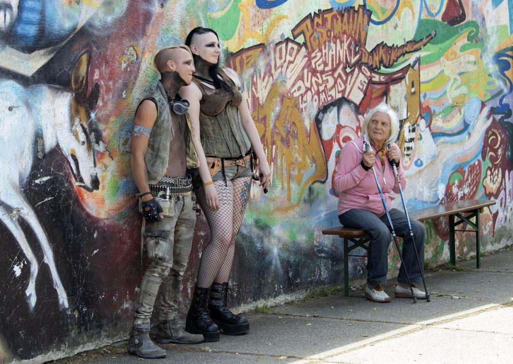 Le ragazze si fotografano presso il murales nel giorno del Wave Gothic Festival a Lipsia, Germania.